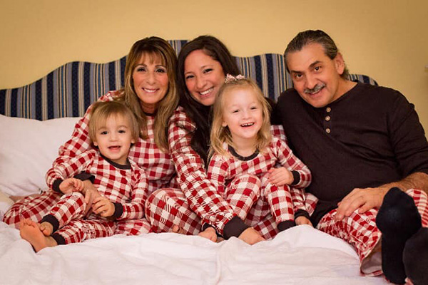 The Shortt family sitting together on a bed in their plaid flannel pajamas