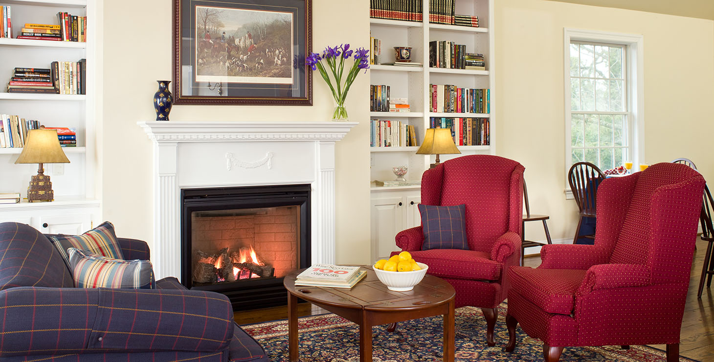 Sitting area by fire in the breakfast room, with red armchairs and purple couch