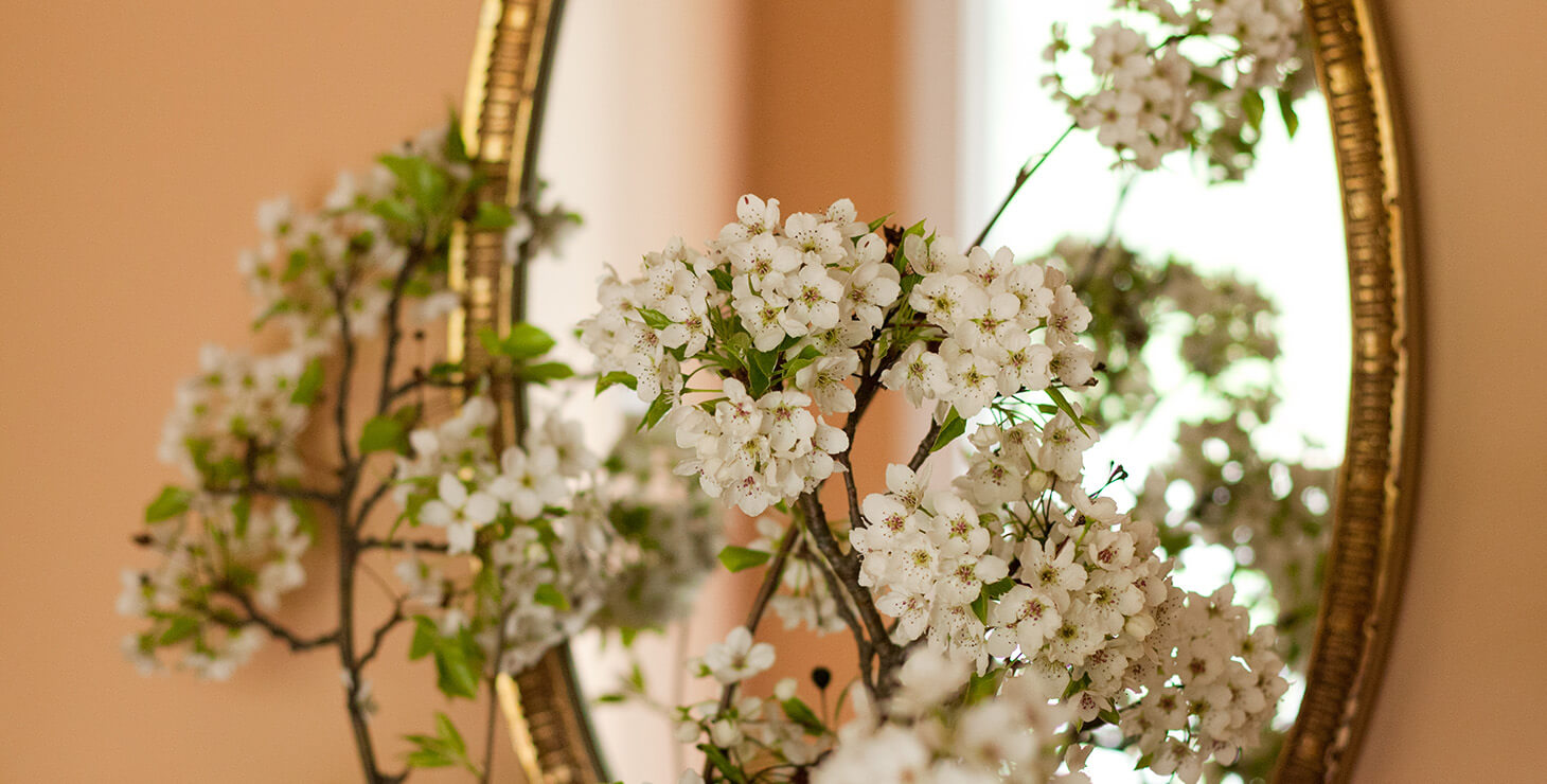 Vase of small white flowers sits in front of a mirror