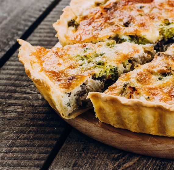 Fresh, warm vegetable quiche on a wooden plate