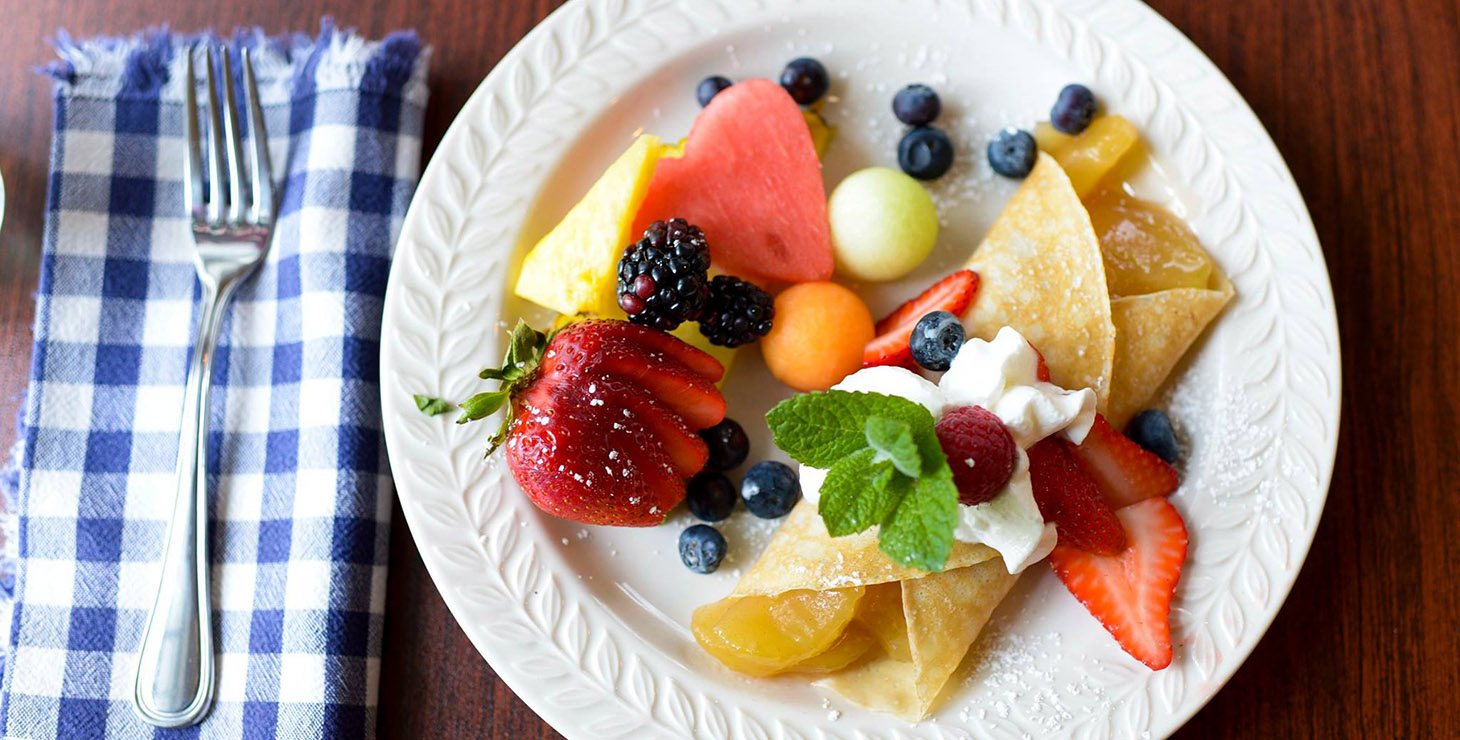 Plate of fresh breakfast fruits and crepe