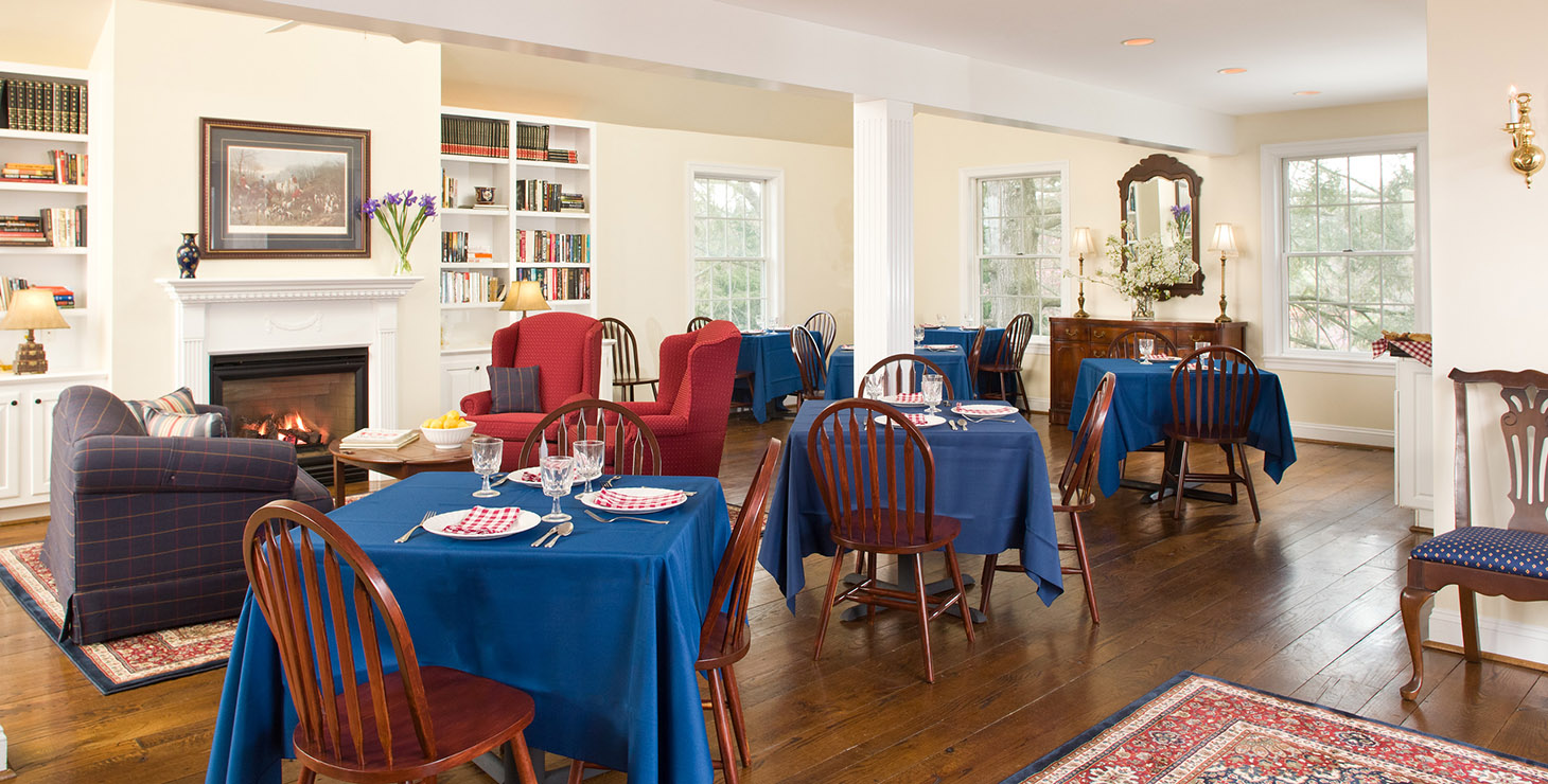 Dining room with blue tablecloths, wooden floors, and high ceilings