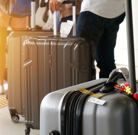 Travelers in line at an airport with suitcases