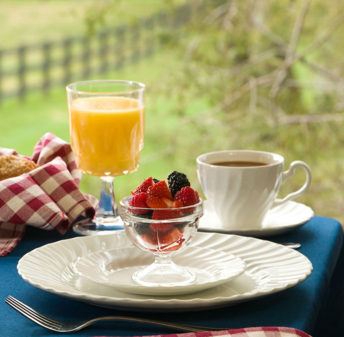 Cups of orange juice, coffee, and fruit sit on a breakfast table by an open window overlooking green fields