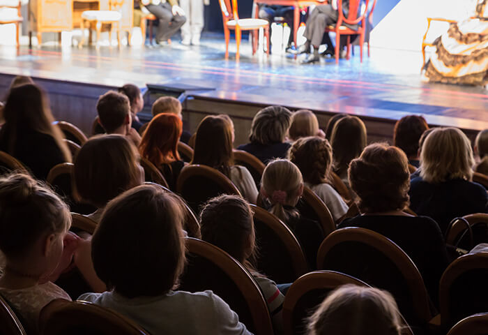 Audience watching a play in a theater