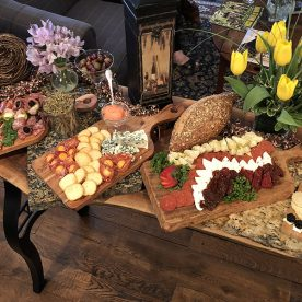 Trays of charcuterie, cheeses, and breads on a table next to couches and flower vases