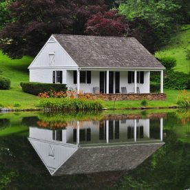 Exterior of the Pond House, a small white building directly next to the lake with a steep roof and orange flowers out front