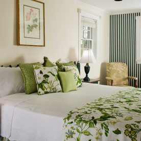 Soft bed in vintage-decorated room with flowers and small cushioned chair in the Pond Room