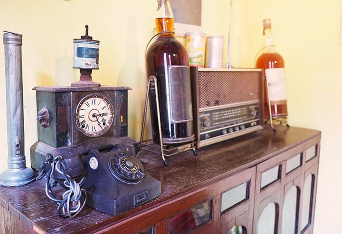 Vintage telephone, whiskey, and radio on table