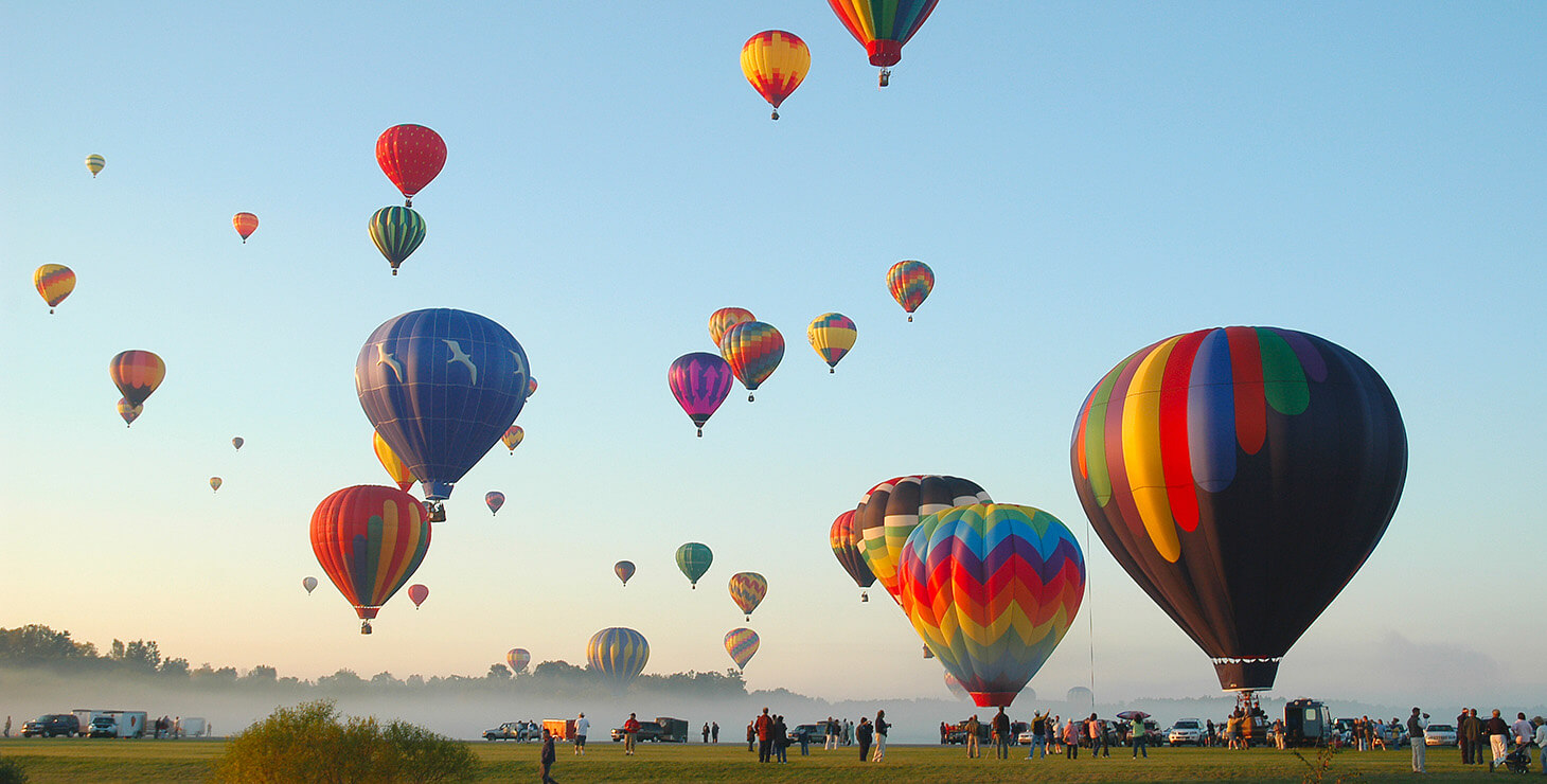 Many hot air balloons rise into the sky at a balloon festival