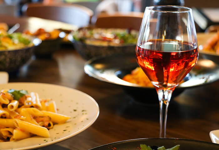 Wine glass by plate of pasta on covered dinner table
