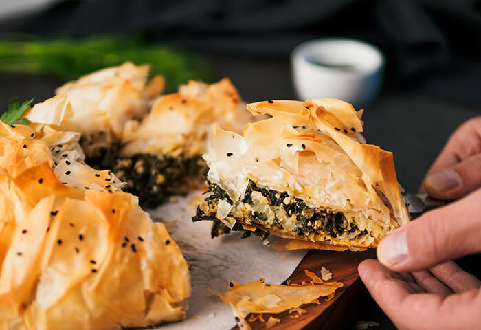 Hand lifting slices of spanakopita