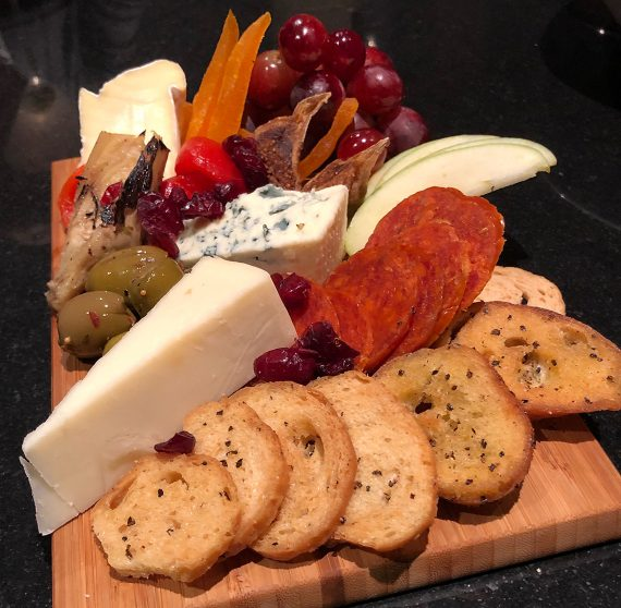 Cheese, bread, meats, and fruit on a platter