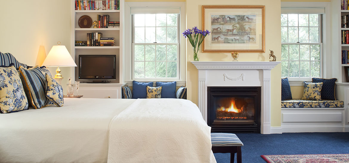 Soft white bed near window sitting area and fireplace