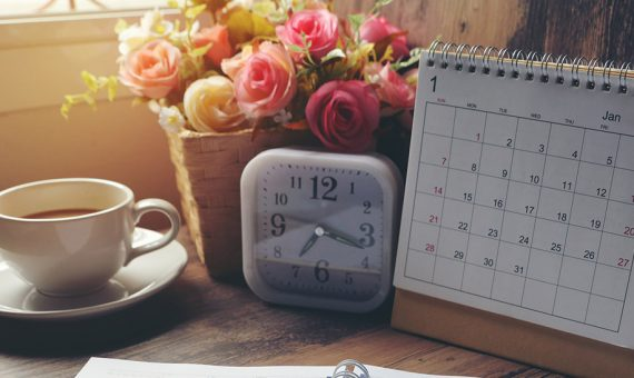 A calendar, small clock, vase of flowers, and coffee cup sit together on a table at sunset