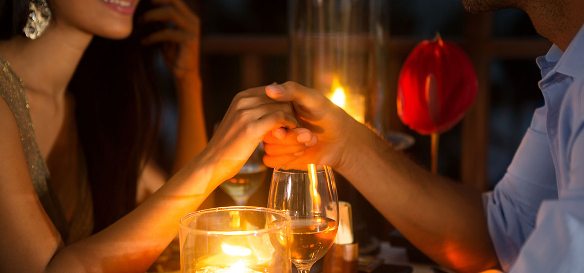 Couple hold hands at romantic candlelit dinner