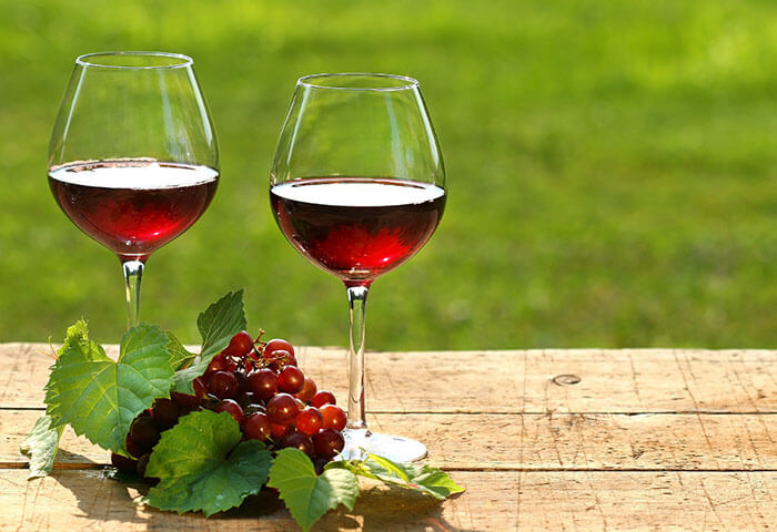 Pair of wine glasses filled with red wine sit on table outdoors next to grapes