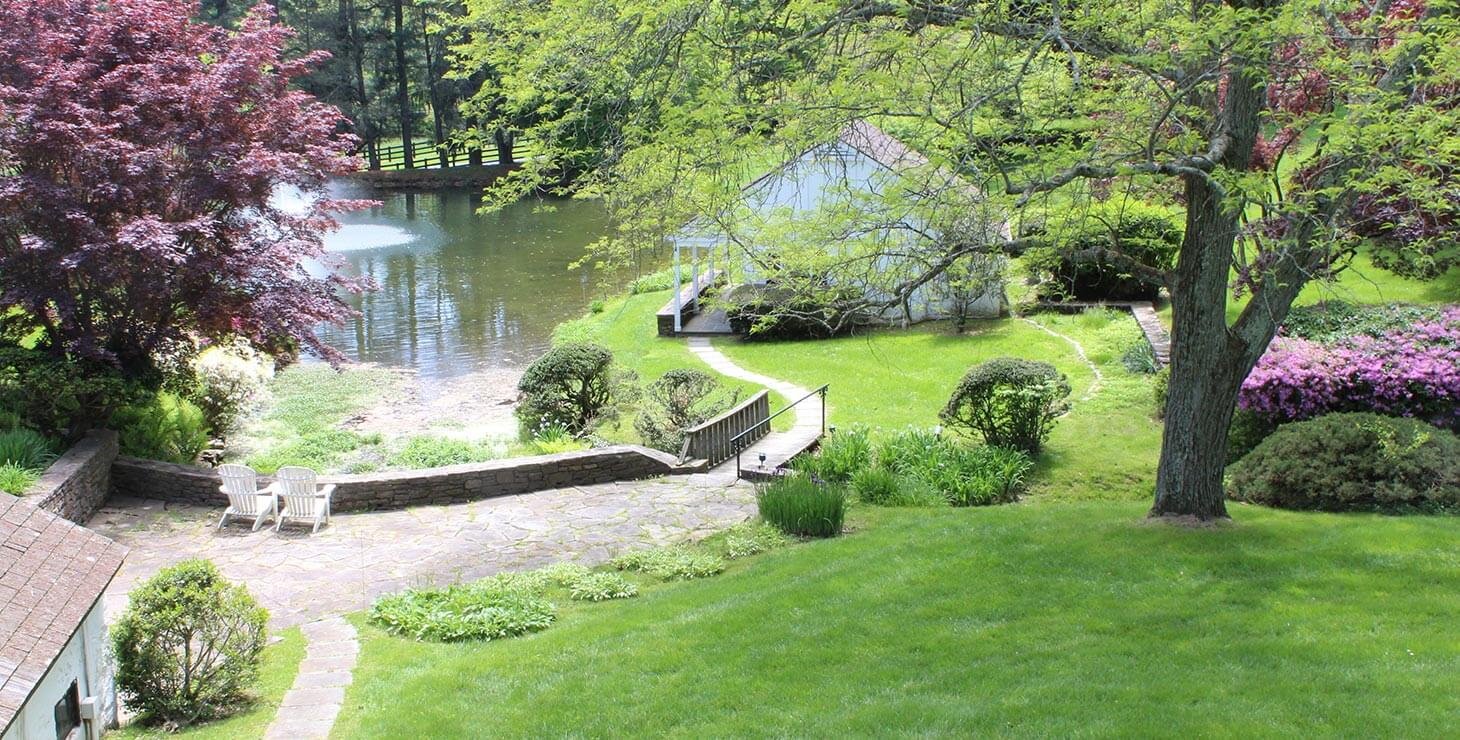 Stone walkway leading down past lawns and small building out past lake