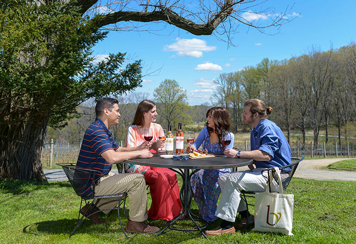 Friends enjoying wine outside at the Galer Estate winery.