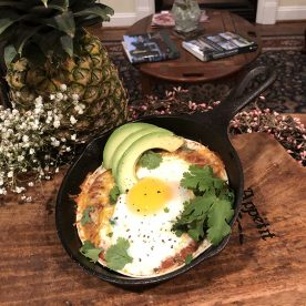Fried egg with avocado and herb toppings in a pan