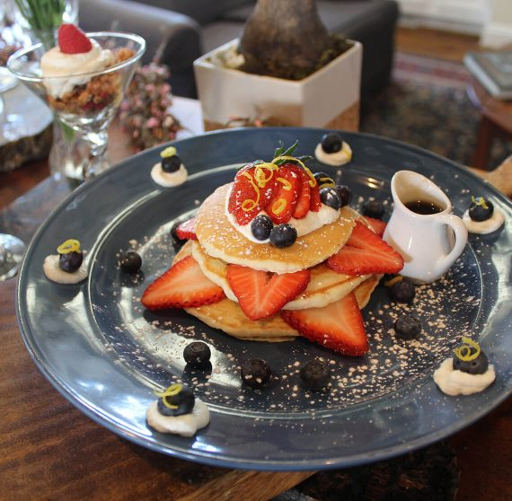 Pancakes and fruit on a blue plate