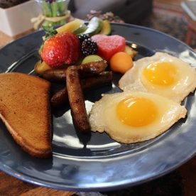 Eggs, toast, sausage links and fruit breakfast